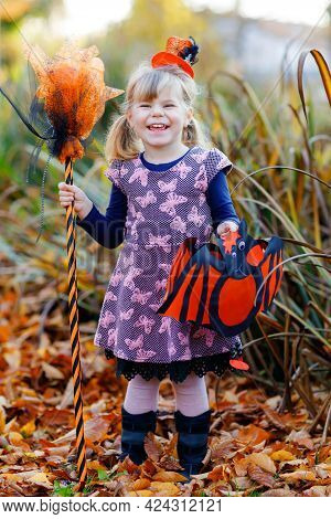 Cute Little Toddler Girl Dressed As A Witch Celebrate Halloween. Happy Child Outdoors, With Orange F