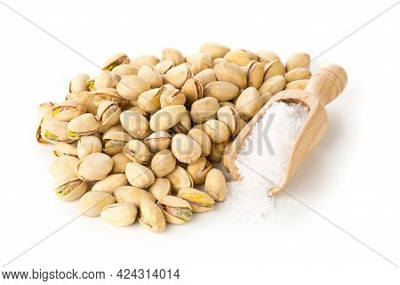 Heap Of Salted, Roasted Green Pistachio Nuts Snack Over White Background With Sea Salt In Wooden Sco