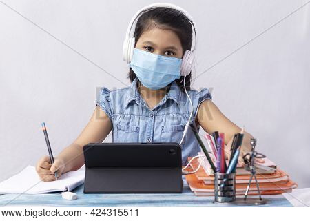 A Pretty Indian Girl Child Attending Online Class With Tablet And Headphone On White Background