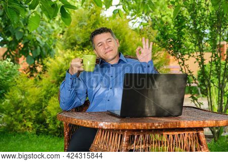 Smiling Mature Caucasian Man Greets With Hand To Business Partner Via Laptop In Home Garden. Remote