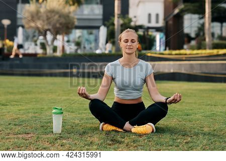 A Young Woman Sits In The Lotus Position On The Lawn In The Park Next To The House And Meditates Aft