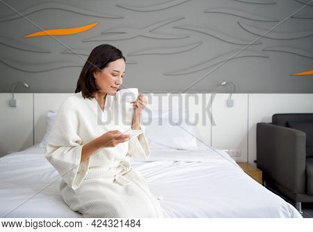 Asian Woman In A Bathrobe Drinking Hot Coffee On Bed In The Morning.