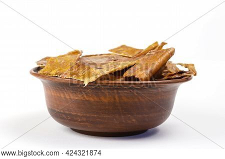 Dried Dog Treats In A Brown Clay Bowl On A White Background. Thin Slices Of Dehydrated Cow Udder. Tr