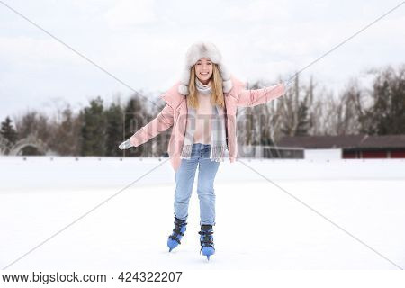 Happy Woman Skating Along Ice Rink Outdoors