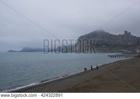 Sudak, Crimea - April 23, 2021: Three People Walk Along An Empty Beach In The Bay Of The Resort Town