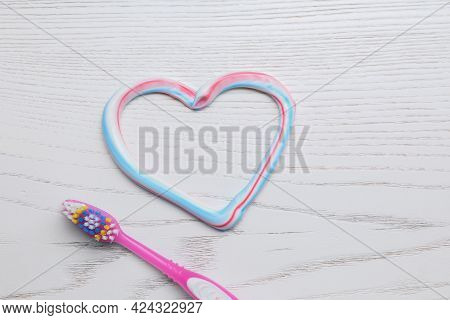 Heart Made With Toothpaste And Brush On White Wooden Background, Flat Lay