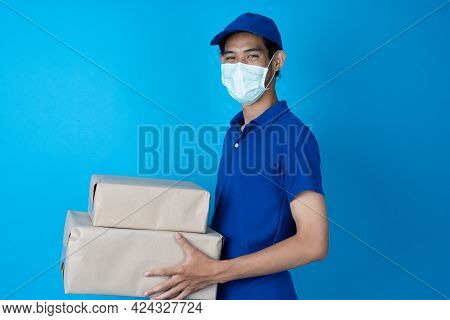 Delivery Man Wearing A Blue Uniform. Sender Wears A Surgical Mask To Prevent Infection With The Pand