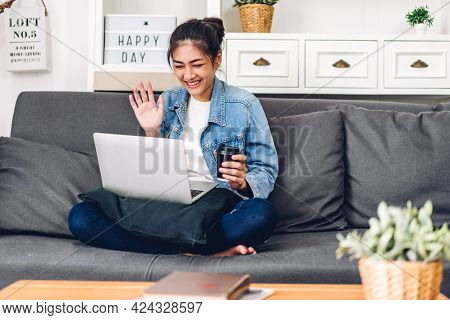 Young Smiling Asian Woman Using Technology Of Laptop Computer Working And Video Conference Online Me