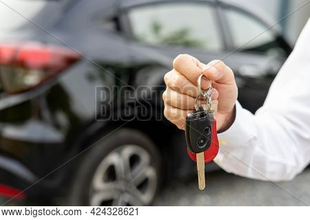 Selling Car, Car Sale, Deal Concept The Dealer Gives The Car Keys To The New Owner Or Renter With An