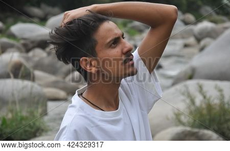 A Handsome Indian Young Guy Standing Beside Of River With Wearing White T-shirt With Passing His Han