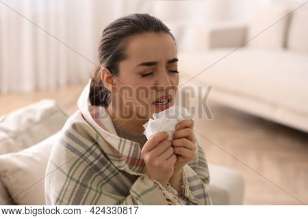 Young Woman Suffering From Runny Nose In Living Room