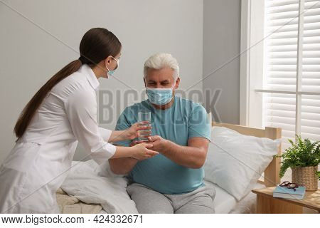 Doctor Giving Water To Senior Man With Protective Mask At Nursing Home