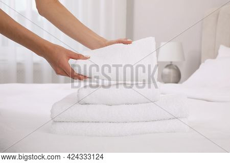 Chambermaid Putting Fresh Towels On Bed In Hotel Room, Closeup