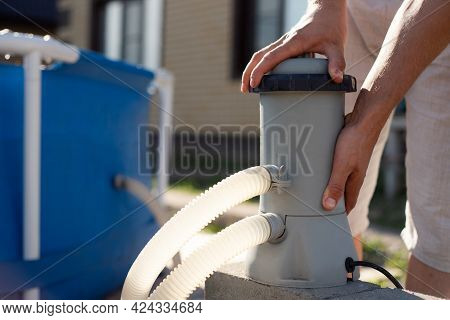 A Man Checks A Filter For Cleaning A Home Pool. Keeping The Swimming Pool Clean