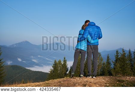 Rear View Of Couple In Love Who Standing On Mountain, Watching Around Beautiful Mountain Scenery And