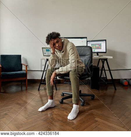 Anxious Young Guy, Investor In Despair After Stock Market Failure, Sitting At Desk, Trading Online F