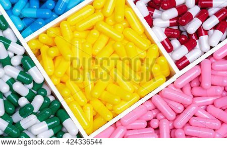 Top View Colorful Capsule Pills In A Plastic Tray. Yellow, Pink, Red, Green, And Blue Capsule Pills.