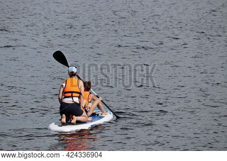 Woman With Two Kids In Life Jackets Swimming With Paddle On A Board In A Water. Standup Paddleboardi
