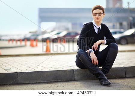 Businesswoman In Glasses Sitting
