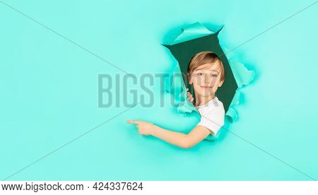 Kid Looks Through Hole. Blonde Boy Looks Through Ripped Paper. Boy In Red Paper Hole Pointing With F