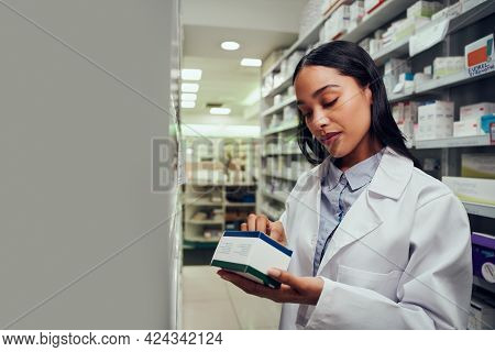 Woman Checking Medicine Box Reading Expiry Date And Instructions Standing In Aisle Of Chemist
