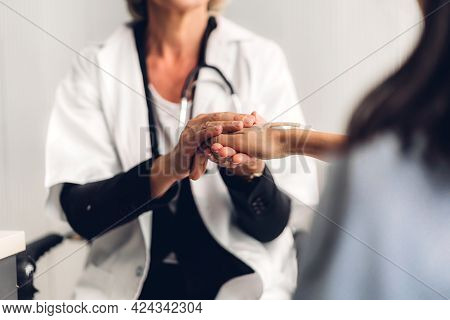 Woman Doctor Consulting And Holding Hand Patient Reassuring With Care On Doctors Table In Hospital.h