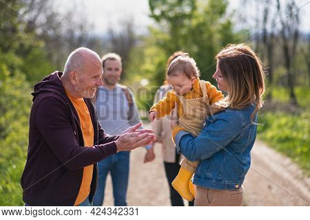 Multigeneration Family With Toddler On A Walk Outdoors In Nature, Having Good Time.