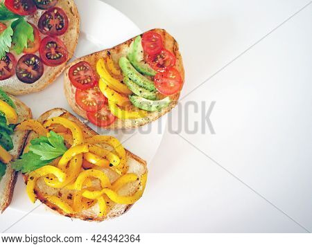Vegan Bruschetta. Delicious Bruschetta With Tomatoes, Yellow Peppers And Avocado On A White Plate. A