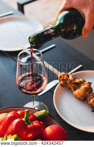 Sommelier Pours Wine Into A Glass At Sunset. Red Wine With Dinner On The Summer Terrace. Meat With R