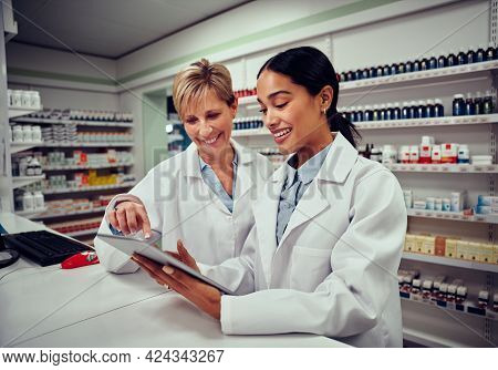 Happy Senior Female Pharmacist Explaining Job And Inventory System To Young Colleague Wearing Labcoa
