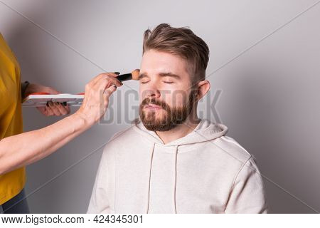 Professional Make-up Artist Doing Young Man Makeup In Studio