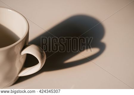 Coffee Cup With Long Shadow Cream Color Side View. Focus On Cup. Morning Energy