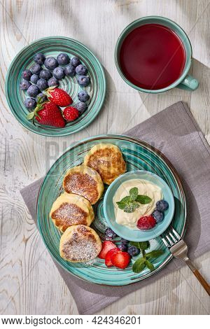 Russian cottage cheese pancakes (Syrniki) with berries and sour cream, cup with fruit tea on light wooden table with sunlight from window. Top view. Healthy breakfast. Serving food