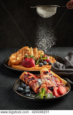 Pancakes with berries  and sweet sauce on black background.  Maslenitsa. Shrovetide. Shrove Tuesday. Pancake Day. Happy holiday, Serving food. Sprinkle the pancakes with powdered sugar