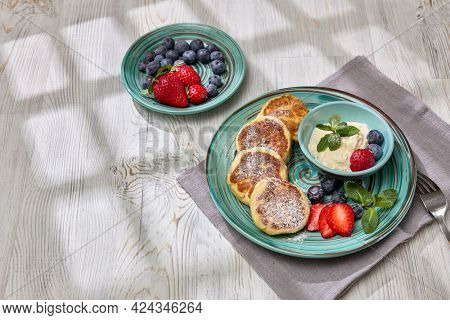 Russian cottage cheese pancakes (Syrniki) with berries and sour cream on light wooden table with sunlight from window. Top view. Healthy breakfast. Serving food