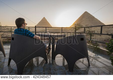 Solo Travellers. A Lone Man Sits On The Roof Of A Restaurant And Enjoys A Beautiful View Of The Grea