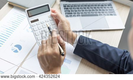 Businessman presses a calculator to calculate earnings and analyze company earnings in his private o