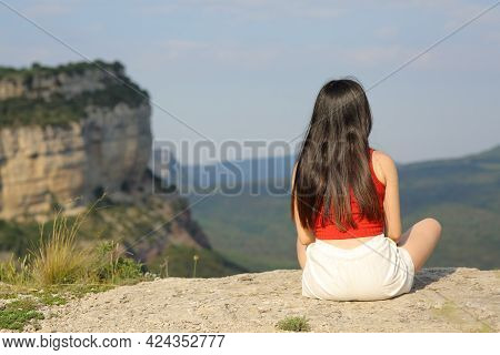 Back View Portrait Of A Woman Sitting Contemplating Views In The Mountain