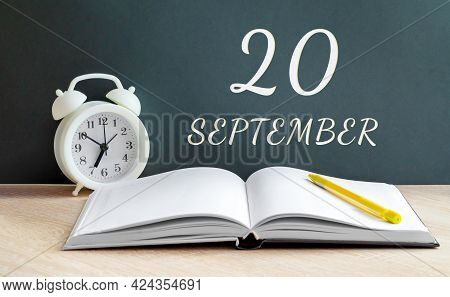 September 20. 20-th Day Of The Month, Calendar Date.a White Alarm Clock, An Open Notebook With Blank