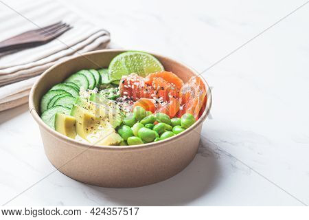 Poke Bowl With Rice, Salmon, Edamame Beans, Cucumber And Avocado In A Reusable Cardboard Bowl. Hawai
