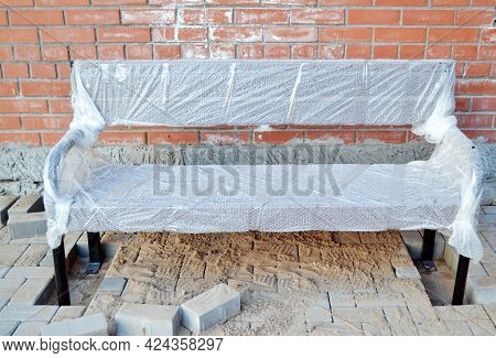 A New Wooden Bench Against The Brick Wall.installation, Installation Or Repair Of A Bench In The Cou