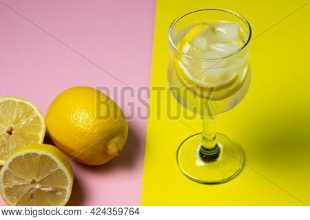 Refreshing Cocktail With Ice And Lemon On A Colored Background. Non-alcoholic Cocktail.