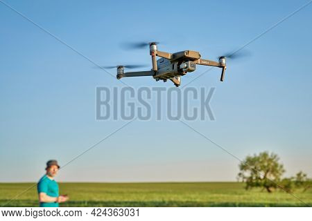 Briggsdale, CO, USA - June 8, 2021:  Radio controlled DJI Mavic 2 Pro quadcopter drone is flying over green prairie with a out of focus male pilot in background.