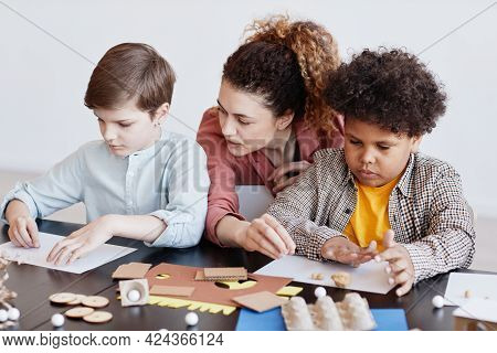 Portrait Of Two Kids Making Cardboard Models During Art And Craft Class In School With Female Teache