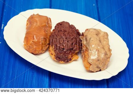Eclairs On White Dish On Wooden Background