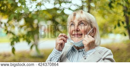Relaxed Woman Takes Off Her Protective Medical Mask From Her Face To Breathe Fresh Air After The End