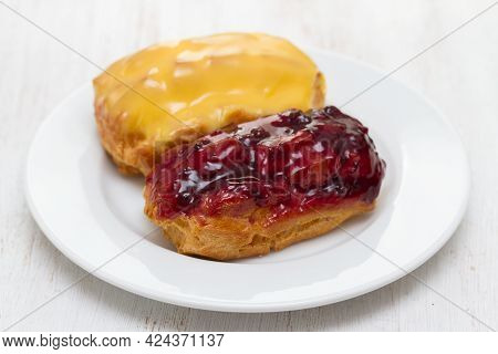 Two Eclairs On White Plate On Wooden Background