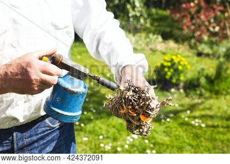 Hands Of Beekeeper In Protective Clothing Switching On The Smoker With Lighter And Paperboard While