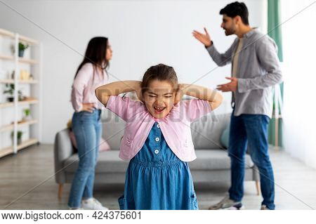 Family Argument Concept. Crying Little Eastern Girl Covering Ears Not To Hear Parents Quarrels, Sele