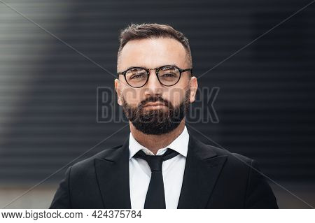 Business And Entrepreneurship Concept. Portrait Of Confident Businessman In Glasses And Black Suit L